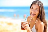 Beach woman drinking cold drink beverage having fun at beach party. Female babe in bikini enjoying I