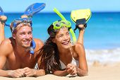 Beach travel couple having fun snorkeling. Happy young multiracial couple lying on summer beach sand