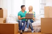 moving, home, technology and couple concept - smiling couple relaxing on sofa with laptop in new hom