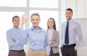 office, business and teamwork concept - friendly young smiling businesswoman with team on back showing ok-sign