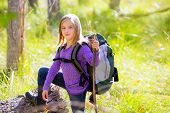 Hiking kid girl with backpack in autum poplar trees forest and walking stick