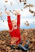 Happy Seven Year Old Girl Playing In Pile Of Leaves poster