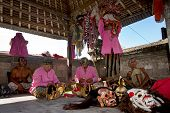 BALI - APRIL 13, 2014: Balinese actors prepare with costume change and make-up before commencing a '