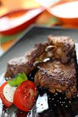 Grilled beef steak with tomatoes and mozzarella.