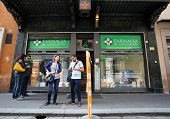 BOLOGNA, ITALY - APRIL 19, 2014: Pedestrians walk past a pharmacy in Bologna, Italy, on Saturday, April 19, 2014.