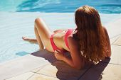 Pretty Young Lady Enjoying Sunbath By Swimming Pool