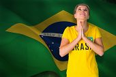 Nervous football fan in brasil tshirt against digitally generated brazil national flag