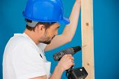 Carpenter or builder wearing a hardhat standing in front of a blue wall drilling a hole in a plank o