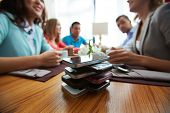 pic of handphone  - Stack of cellphones with group of friends on background - JPG