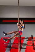 Rope Climb exercise woman workout at gym climbing