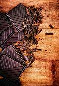 Chopped Chocolate Bar On Wooden Background Closeup. Broken Dark Chocolate Bar On Wood Table Macro.