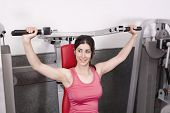 image of spandex  - Woman posing in gym room ready for shoulder fitness exercises - JPG