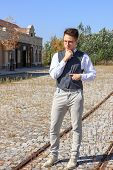 Man In Shirt And Vest With Bow Tie And Glasses, Standing In Lines Of Railway In The Old Town