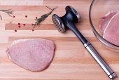 Raw pork schnitzel with meat tenderizer on wooden board