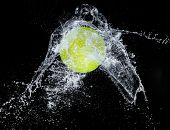 Water splash with sport ball on black background