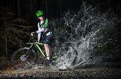 Mountain biker speeding through forest stream, water splash in freeze motion.