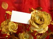 Golden roses and postcard on red background