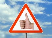 Triangle sign with hand (okay), sky background