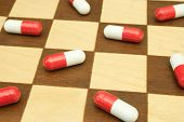 Pills on chessboard, close-up