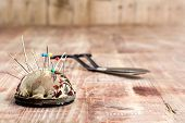 Old Scissors And Pincushion On A Wooden Background
