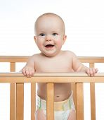 Infant Child Baby Toddler In Wooden Bed Looking Up Happy Smiling
