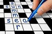 Hand filling in crossword - summer vacation concept