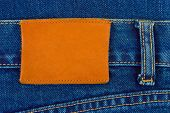 Blank leather label on blue jeans, fashion background