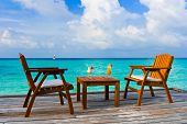 Two cocktails on table, beach cafe, sea background