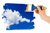 Hand with paintbrush painting sky isolated on white background