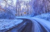 foto of icy road  - Icy road with yellow traffic sign with snow and trees - JPG