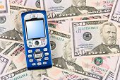 Mobile phone on money background - business concept