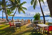 Cafe and palms on a tropical beach - travel background