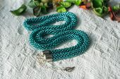 Green-blue Necklace From Beads On A Textile Background