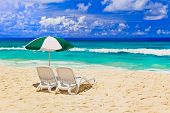 Chairs and umbrella at tropical beach - vacations background