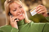 Cheerful Woman Using Her Phone With Credit Card