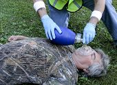 image of cpr  - Paramedic giving CPR to a man using an Ambu bag - JPG