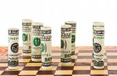 Money on chess board isolated on white background