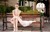 Young beautiful ballerina relaxing on bench