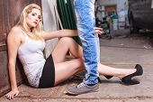 stock photo of jeans skirt  - Man stands with his legs in jeans wearing on the young sitting woman whose hand between his legs is - JPG