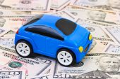 Toy car on money background - business concept