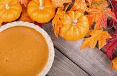 picture of pumpkin pie  - Pumpkin pie with pumpkins and leaves on a wood background - JPG