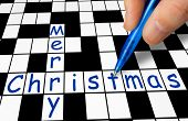 Hand filling in crossword - Merry Christmas - holiday concept