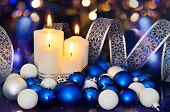 Lighted Candles And Blue White Christmas Tree Decorations On The Bokeh Background