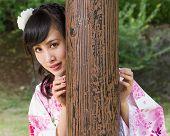 Asian Woman In Kimono Behind Wooden Pillar