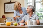 Happy Mature Wife Serving Bread To Her Husband For Breakfast