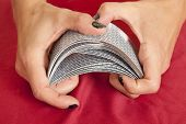 Hands Shuffling Cards On Red