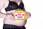 pregnant woman clothed in black bra and jeans holding a toy slate with text