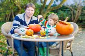 Young Dad And Kid Son Making Jack-o-lantern For Halloween In Autumn Garden