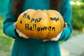 Young girl holding Halloween pumpkin, close-up, outdoors