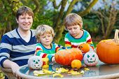 Young Father And Two Siblings Making Jack-o-lantern For Halloween In Autumn Garden